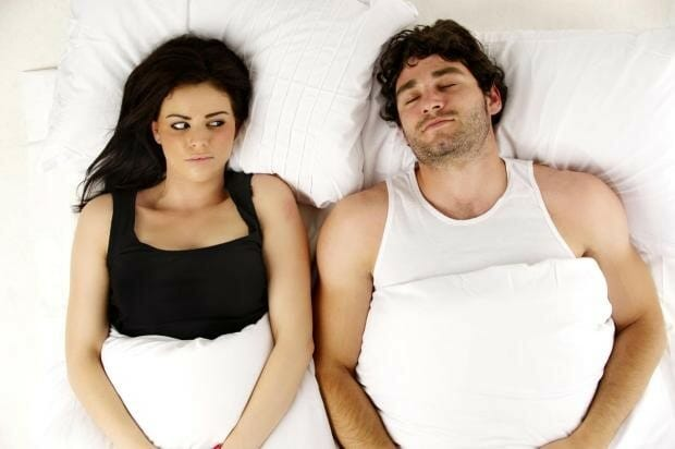 woman-laying-next-to-her-snoring-husband
